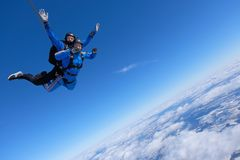 Tandem skydiving. Two guys are in the blue sky. Skydiving. Tandem jump. Two guys are having fun in the sky royalty free stock photography