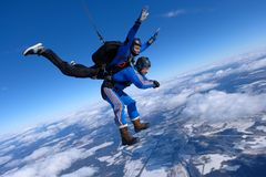 Tandem skydiving. Two guys are in the blue sky. royalty free stock photo