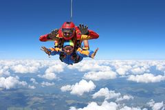 Tandem skydiving. Instructor with sexy girl. royalty free stock photography