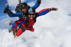Skydiving. Tandem is flying in the clouds. royalty free stock image