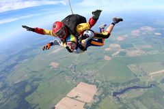 Tandem skydiving. Woman and instructor are flying in the sky. royalty free stock photography