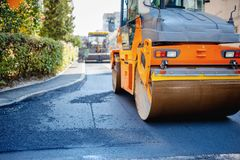 Tandem vibration roller compactor working on asphalt pavement Stock Image