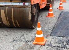 Tandembodenverdichter- und Verkehrskegel auf dem Straßenbau Stockfoto
