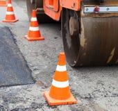 Tandembodenverdichter- und Verkehrskegel auf dem Straßenbau Lizenzfreie Stockfotografie