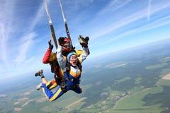 Tandemt hoppa med fritt fall Kvinnan och instruktören är i himlen royaltyfri bild