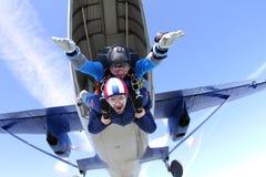 Tandemt hoppa med fritt fall Två grabbar har gyckel i himlen royaltyfri foto