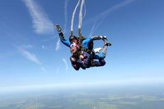 Tandemt hoppa med fritt fall Två grabbar har gyckel i himlen royaltyfri bild