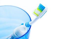 Tandenborstel en tandpasta in blauw plastic glas Royalty-vrije Stock Foto's