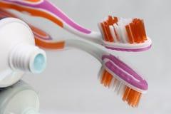 Tandenborstels en tandpasta op een spiegelplank Mondelinge hygiëneproducten stock afbeelding
