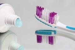 Tandenborstels en tandpasta op een spiegelplank Mondelinge hygiëneproducten royalty-vrije stock foto's