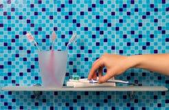 Tandenborstels op badkamersplank stock afbeeldingen
