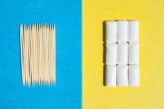 Tandenstokers op blauwe kauwgom als achtergrond en groeps in witte container op gele achtergrond, hoogste mening stock fotografie
