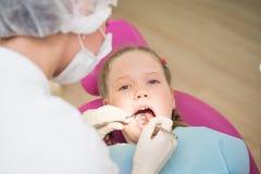 Tandexamen, klein meisje in tandkliniek Stock Foto's