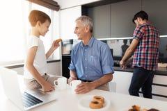 Tandis que l'homme lave des plats, son père et fils boivent du thé avec des gâteaux Photo stock