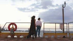 Tandis que l'homme se tient sur le pilier et observe le coucher du soleil, la femme l'étreint de retour banque de vidéos