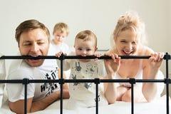 Tandjes krijgenbaby, jonge familie op bed Royalty-vrije Stock Foto's