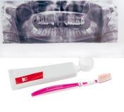 Tandkräm och tandborste på tand- panorama- radiogr för bakgrund arkivfoto