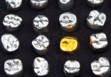 Tandkronor för tand- guld och metallpå mörk svart ytbehandlar Royaltyfri Bild