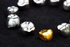 Tandkronor för tand- guld och metallpå mörk svart ytbehandlar Arkivfoto