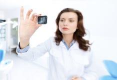 Tandläkare assistent undersöker bilden för x-strålen royaltyfri fotografi
