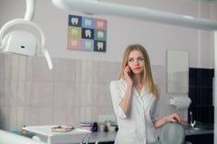 Tandläkare för ung kvinna med mobiltelefonen i det tand- kontoret Royaltyfri Fotografi