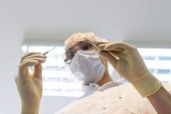 Tandläkare för ung man i skyddshandskar och en maskering Royaltyfri Foto