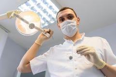 Tandläkare för ung man i skyddshandskar och en maskering royaltyfria foton