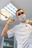 Tandläkare för ung man i skyddshandskar och en maskering royaltyfri bild