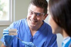Tandläkare Giving Woman Advice på kosmetiskt göra vit för tänder royaltyfri bild