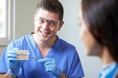 Tandläkare Giving Woman Advice på kosmetiskt göra vit för tänder royaltyfri foto