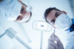 Tandläkare i kirurgiska maskeringar som rymmer tand- hjälpmedel Royaltyfri Fotografi