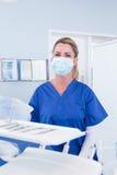 Tandläkare i maskering bak magasinet av hjälpmedel Arkivbild