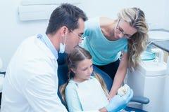 Tandläkare med assistentundervisningflickan hur man borstar tänder Arkivbild