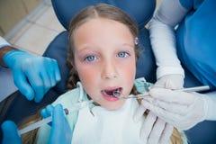Tandläkare med undersökande flickatänder för assistent Arkivbild