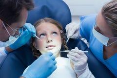 Tandläkare med undersökande flickatänder för assistent Arkivfoton