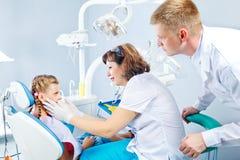 Tandläkare, medicinsk assistent och en unge Arkivbilder