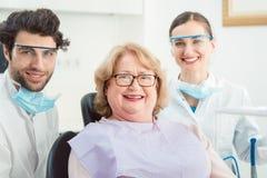 Tandläkare och patient i kirurgi som ser kameran Arkivfoton