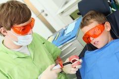 Tandläkare- och tålmodigpojken ser det ljusa hjälpmedlet Royaltyfri Fotografi