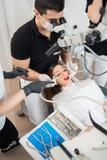 Tandläkare och två kvinnliga assistenter som behandlar tålmodiga tänder med tand- hjälpmedel på det tand- klinikkontoret tand- ut arkivbild