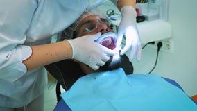 Tandläkare på arbete i kontoret En kvinnlig doktor undersöker tänderna och käkarna av en manlig patient lager videofilmer