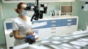 Tandläkare som använder det tand- mikroskopet i tandläkekonst för operation av en kvinnapatient lager videofilmer