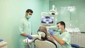 Tandläkare som använder UV lampan för tand- avvänjning på tänder av patienten stock video