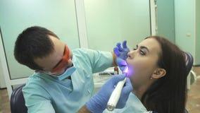 Tandläkare som använder UV lampan för tand- avvänjning på tänder av patienten lager videofilmer