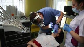 Tandläkare som behandlar tänder för patient` ett s med tand- hjälpmedel i tand- klinik dentistry arkivfilmer