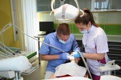 Tandläkare som behandlar tänder för patient` ett s med tand- hjälpmedel i tand- klinik dentistry Arkivbilder