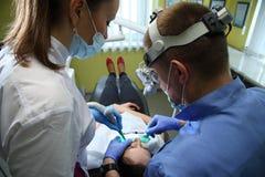 Tandläkare som behandlar tänder för patient` ett s med tand- hjälpmedel i tand- klinik dentistry Royaltyfri Bild