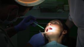 Tandläkare som behandlar tänder för patient` ett s med tand- hjälpmedel i tand- klinik dentistry lager videofilmer