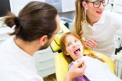 Tandläkare som ger flickabehandling i tand- kirurgi Arkivbilder