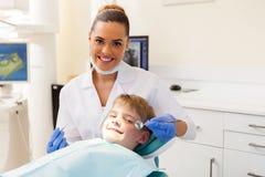 Tandläkare som konsulterar den lilla patienten Arkivbilder