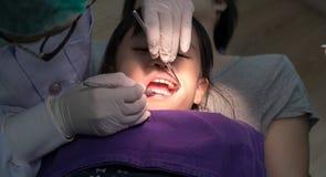 Tandläkare som kontrollerar asiatiska flickatänder royaltyfria foton